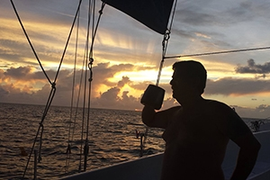 A passenger enjoying the sunrise on one of the Blackbeard's dive liveaboard sailboats