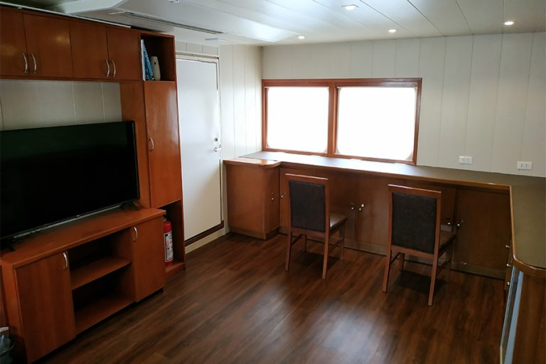 The dive liveaboard All Star Infiniti Vessel Salon with Living and Dining Areas, a Bar, a Large TV and Entertainment Library