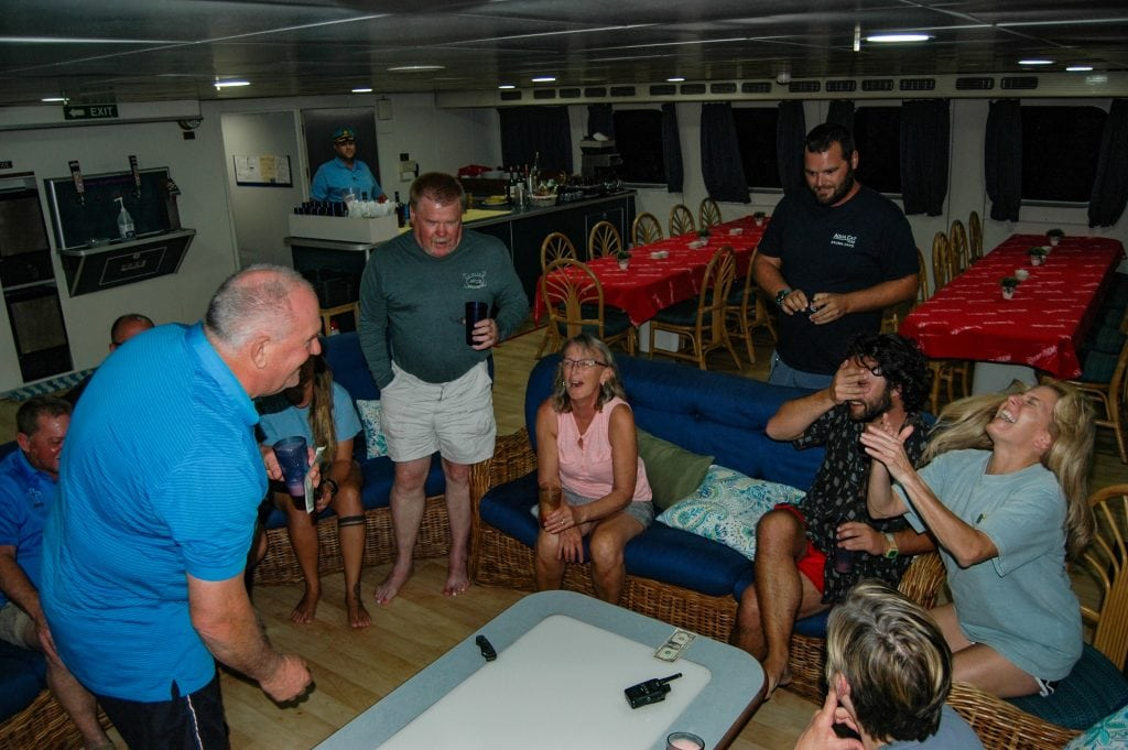 A guest beating me at a dice game aboard Aqua Cat, a Bahamas Liveaboard - Photo cred: Karl Trow